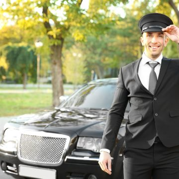 Young chauffeur adjusting hat near luxury car on the street